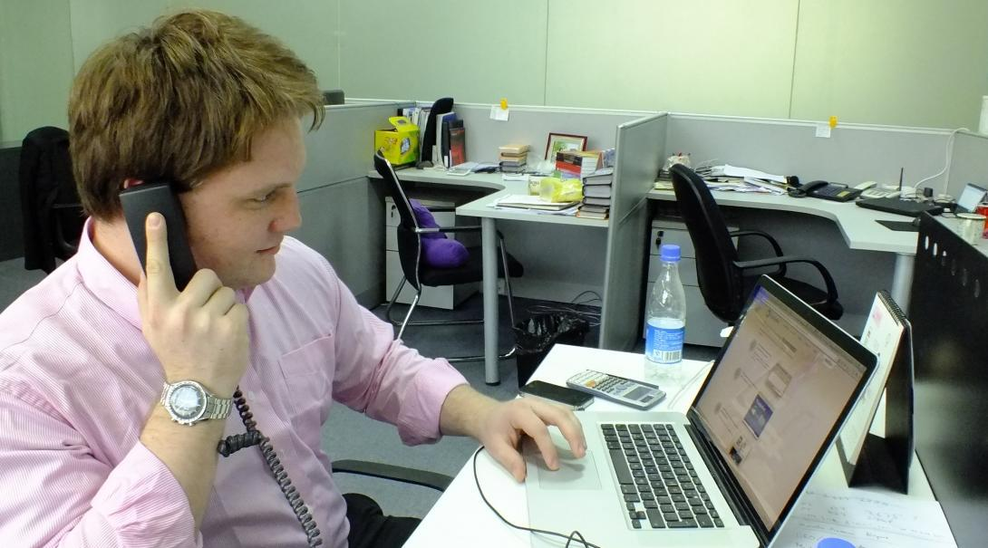 A student doing a Law internship in China discusses a case with a client over the phone in Shanghai.